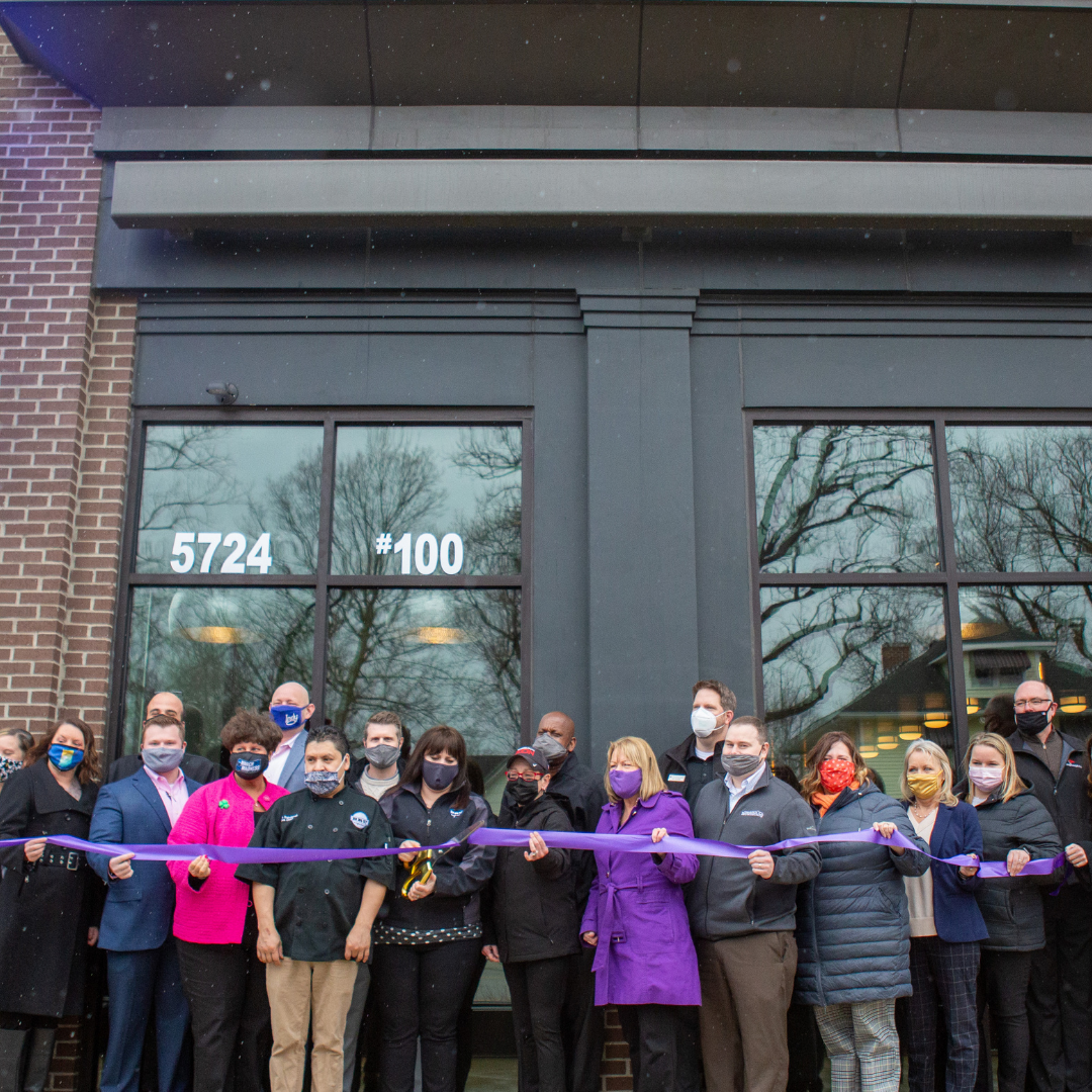 People stand in front of Bru Burger Bar for a ribbon-cutting ceremony